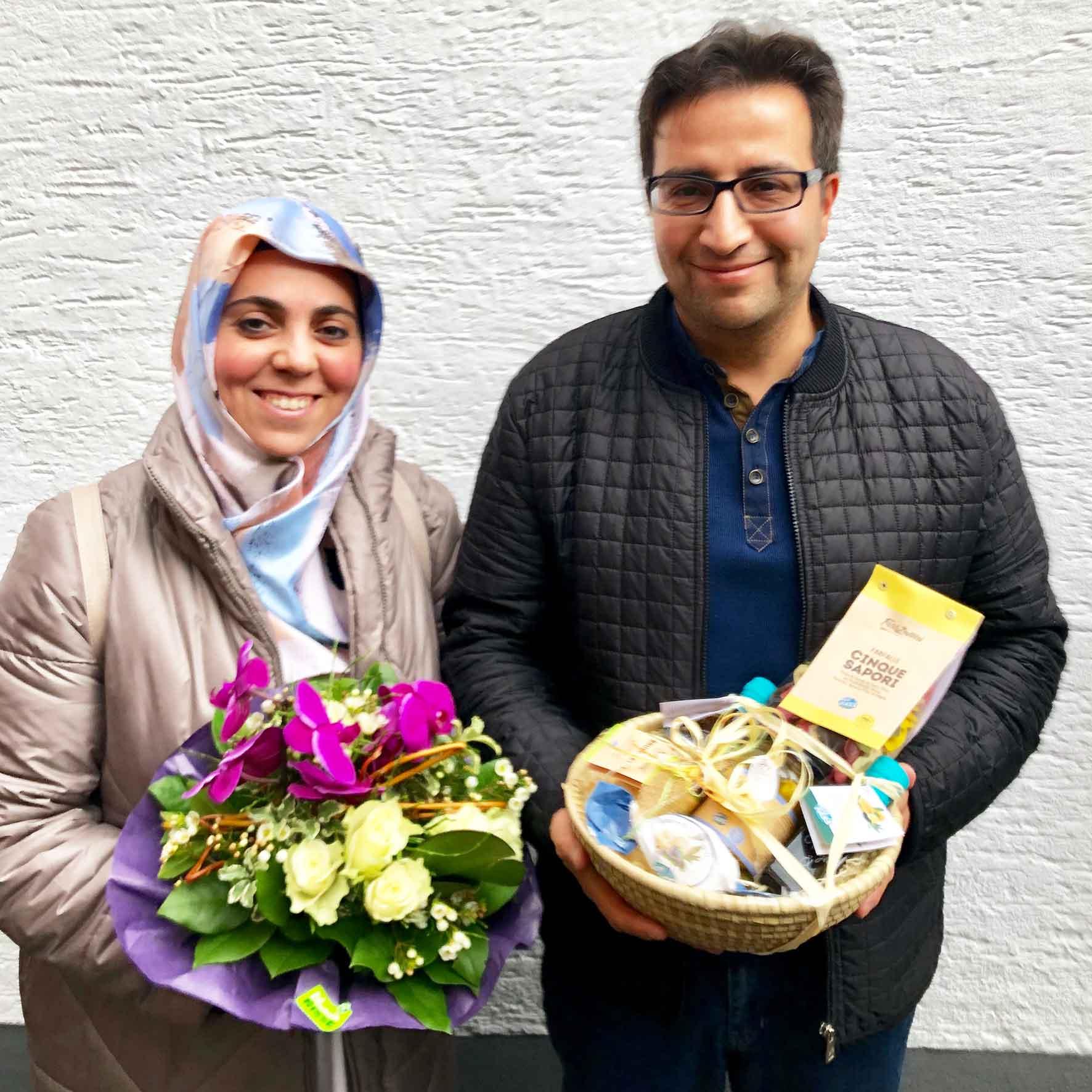 Zufriedene Immobilieneigentümer in Köln Immobilienmakler Köln nach erfolgreichem Notartermin mit überreichtem Blumenstrauß und Geschenkekorb