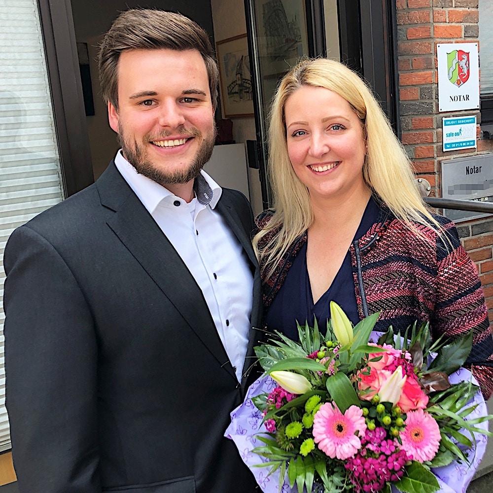 Zufriedene Immobilieneigentümer in Köln Merheim nach erfolgreichem Notartermin mit überreichtem Blumenstrauß