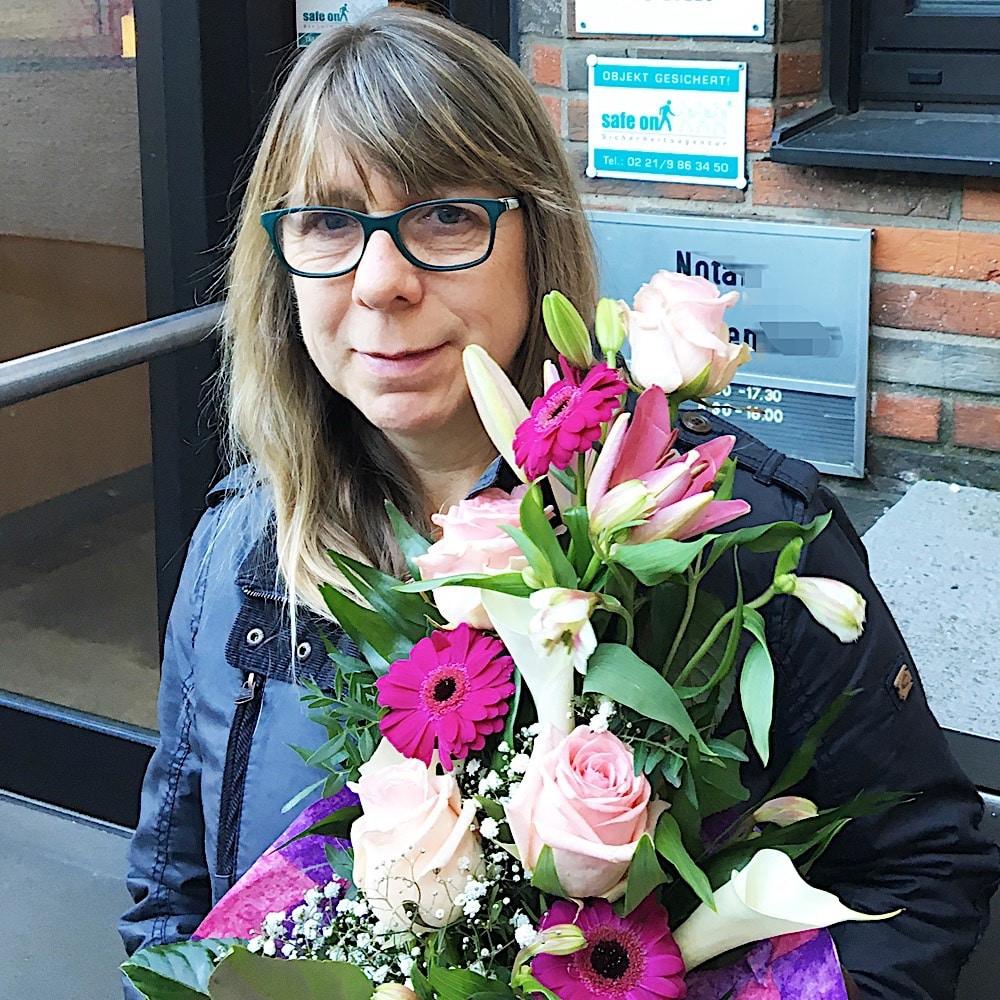 Zufriedene Immobilieneigentümer in Köln Immobilienmakler Köln nach erfolgreichem Notartermin mit überreichtem Blumenstrauß