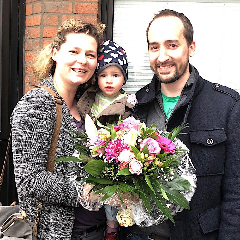 Zufriedene Immobilieneigentümer in Köln Flittard Immobilienmakler Köln nach erfolgreichem Notartermin mit überreichtem Blumenstraußer Notartermin Blumen überreicht