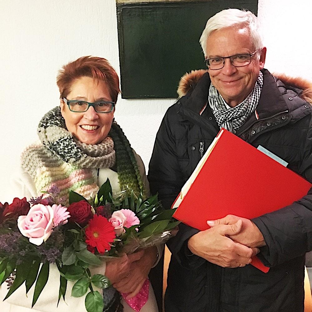 Zufriedene Immobilieneigentümer in Köln Brück Immobilienmakler Köln nach erfolgreichem Notartermin mit überreichtem Blumenstrauß