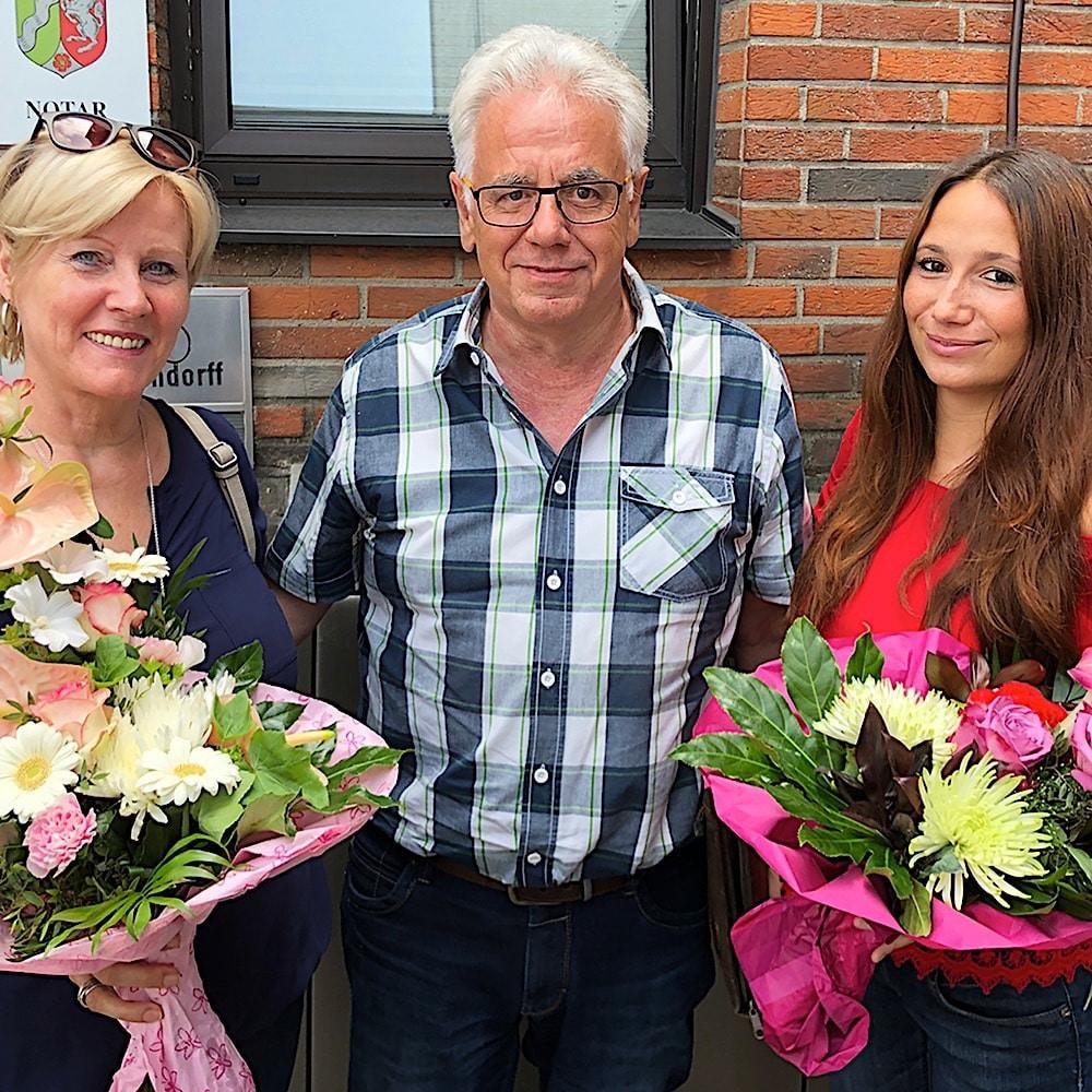 Zufriedene Immobilieneigentümer in Köln Merheim Immobilienmakler Köln nach erfolgreichem Notartermin mit überreichtem Blumenstrauß