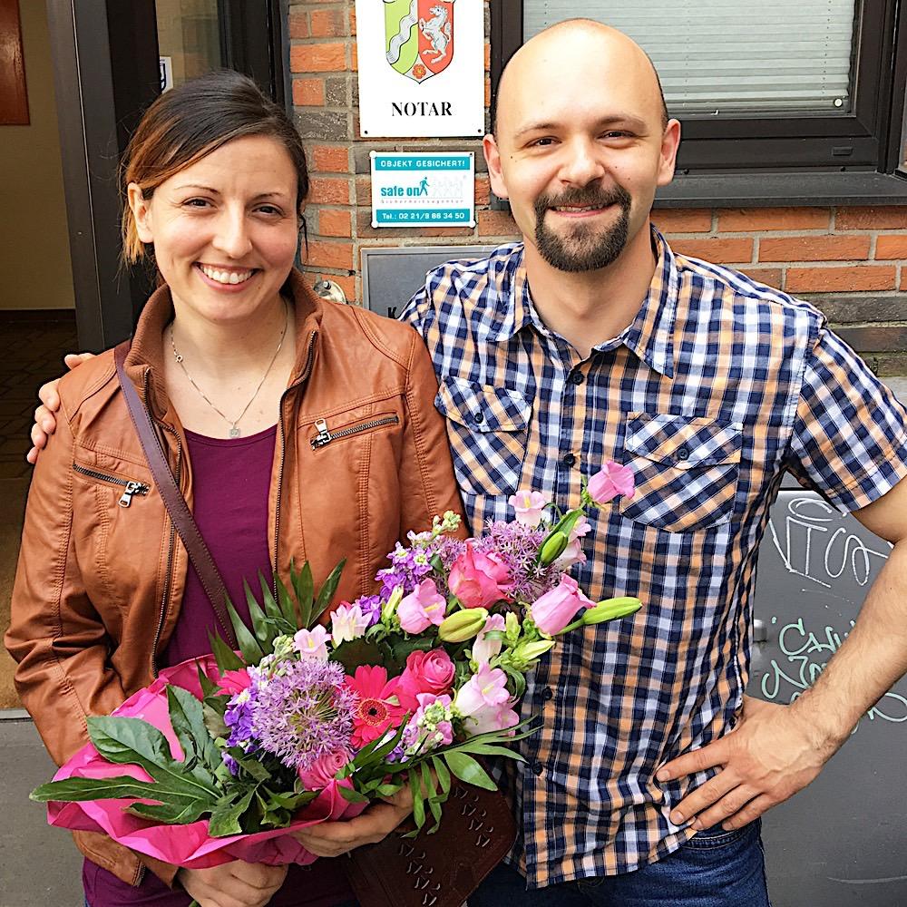 Hausverkauf Köln Immobilie erfolgreich zum besten Preis verkaufen Zufriedene Immobilieneigentümer in Köln Notartermin Blumen überreicht